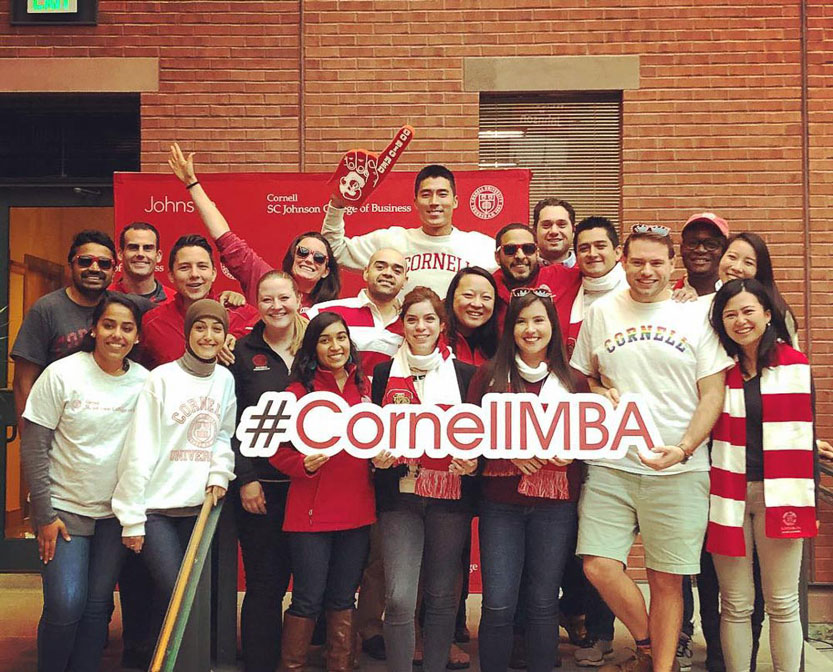 Group of students holding a large #CornellMBA sign