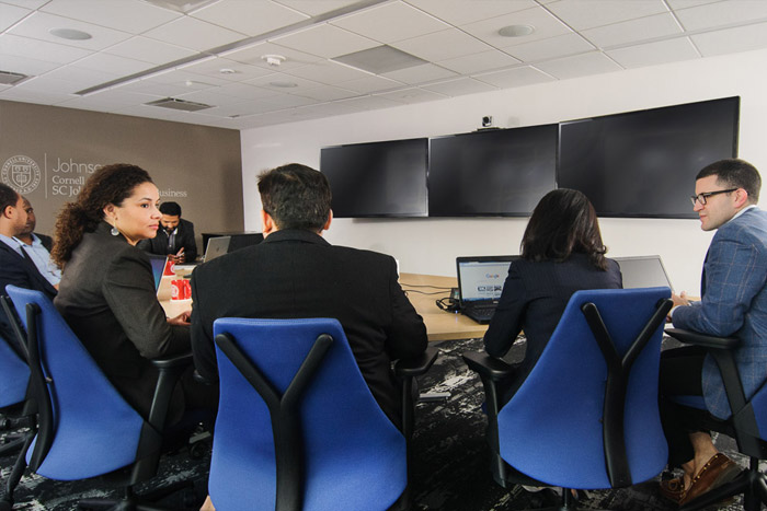 Students facing television monitors while seated around a boardroom table
