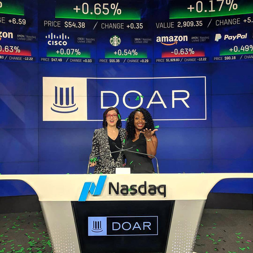 Two students standing at the Nasdaq opening desk