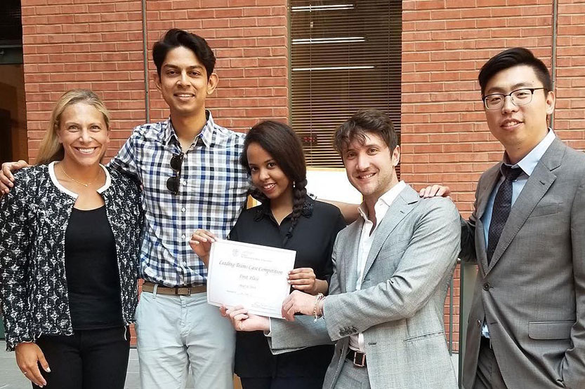 One-year MBA students holding a certificate after winning a competition