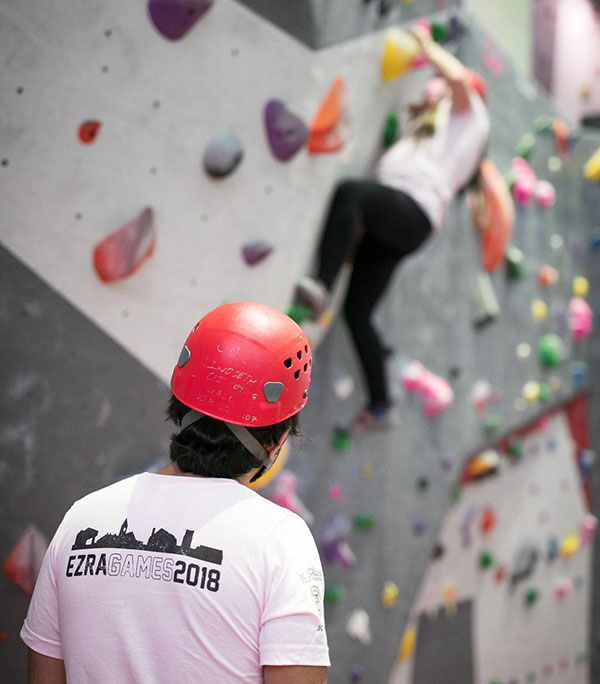 MBA students climbing a rock wall during Ezra Games