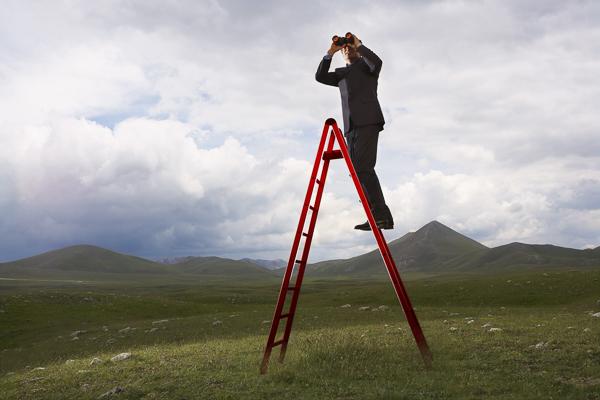 Businessman on ladder looking through binoculars