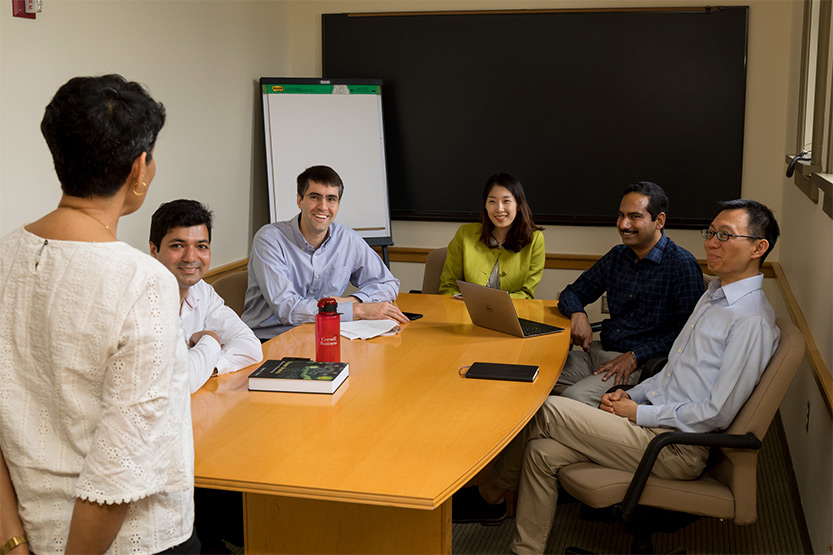 PhD student and four Johnson faculty sit around table while they listen to Nicholas H. Noyes Professor of Management, Vrinda Kadiyali, present
