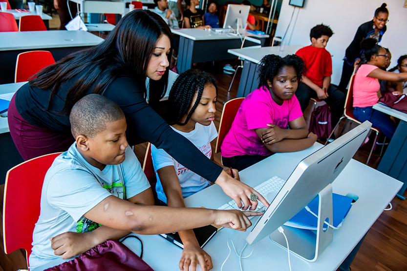 photo of Hilary Lashley Renison standing and leaning between middle-school-aged children who are sitting at a table and looking at a computer monitor, looking at and pointing to the screen