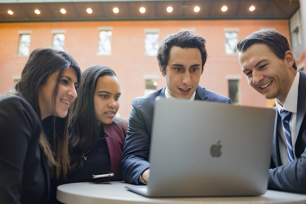 MPS students in discussion looking at a laptop