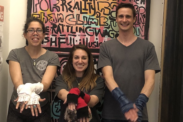 Austin, Alia, and Becki stand in front of colorful art and show their gloves