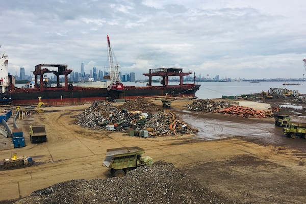 Scrap metal pile with machines and the NYC skyline