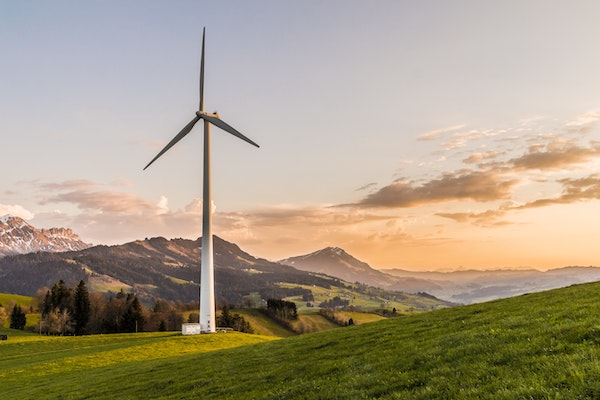 A wind turbine stands amid rolling hills.