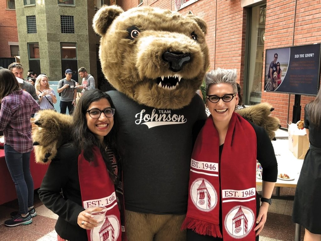 Two women standing with Cornell bear.