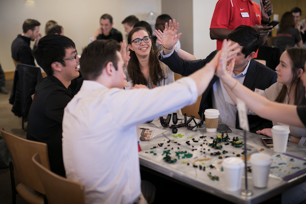 Students high-five over a table of LEGO
