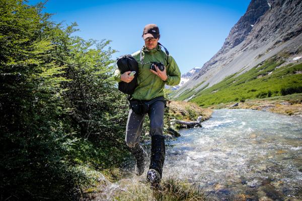 A man crosses a stream in a rugged landscape