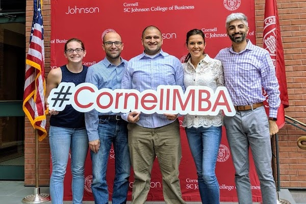Five MBA students pose for a photo