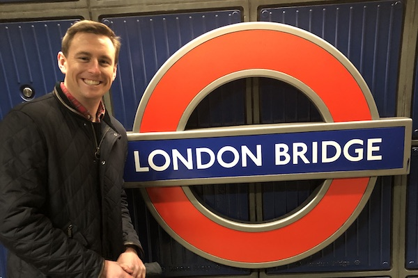 """A student poses for a photo with a London Underground metro sign that reads """"London Bridge."""""""