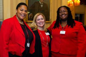 Three women in Cornell red pose for a photo