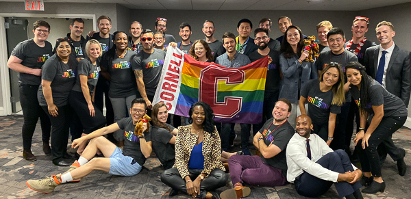 A large group poses with a Cornell rainbow flag