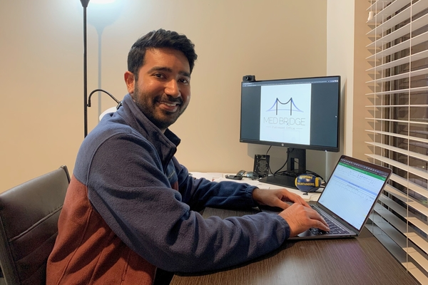 A picture of Rahul Singh sitting at his desk in front of a computer, working from his office