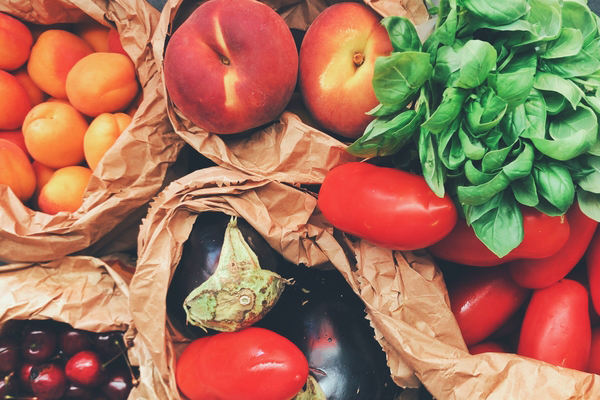 Brown bags filled with fresh fruits and vegetables