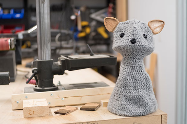 photo of a crocheted social robot that looks like a cat sitting in an engineering fabrication workshop