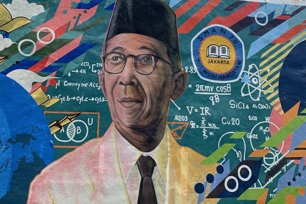 A mural featuring the head of an Indonesian man with glasses, wearing a traditional black peci cap, white jacket and black tie surrounded by colorful educational symbols from math and science.