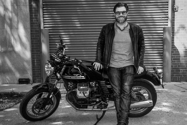 Austin Rothbard leaning against a motorcycle