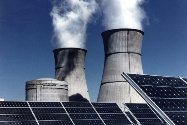 Solar panels with industrial smoke stacks behind them