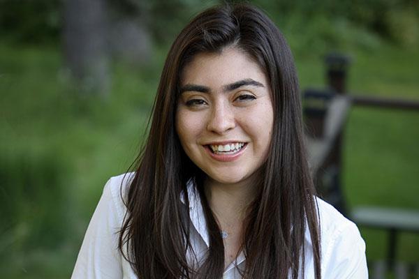 headshot of Marla Beyer, taken outside with green landscape in the background