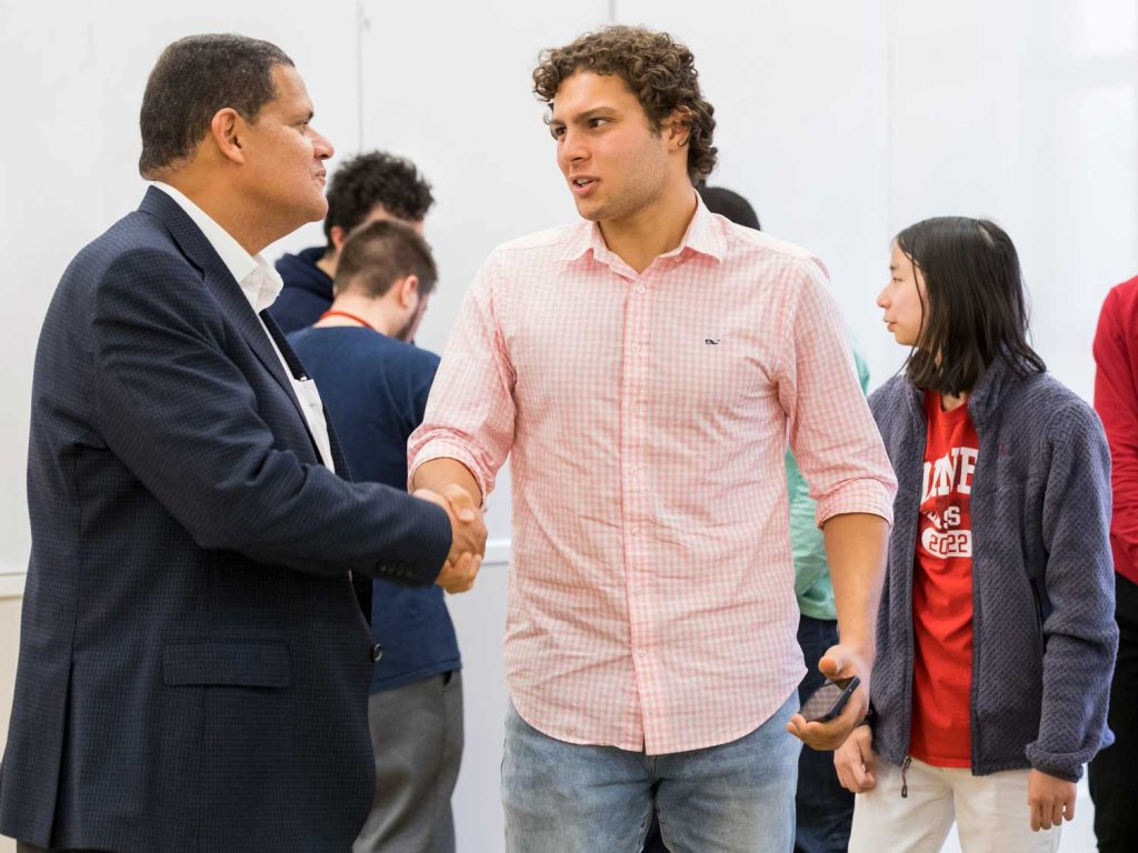 Student shaking the hand of a an alum at a networking event
