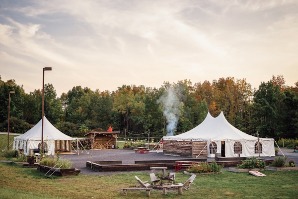 Two large tents one either side of an open area with a fire pit and wooden chairs in the foreground.
