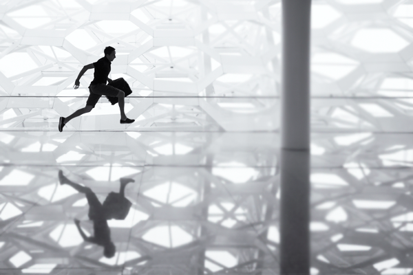 silhouette of man running with a brief case at airport