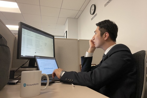 A picture of Duncan Lee working at his cubicle at the NYC office, with an AccountAbility mug.