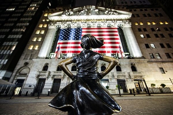 a statue of a girl stands in defiance on WallStreet