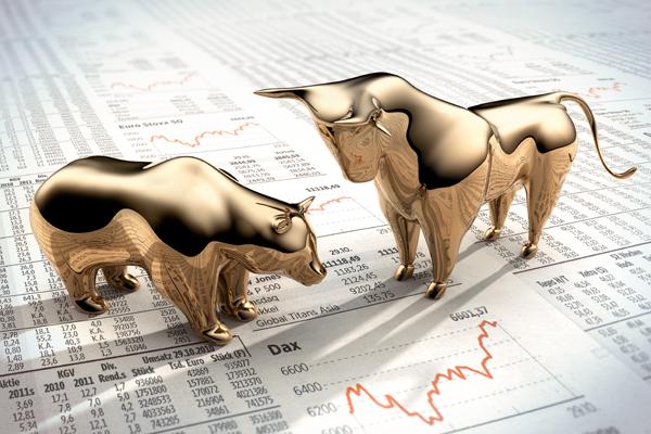 gold bulls figurines on stock market sheet